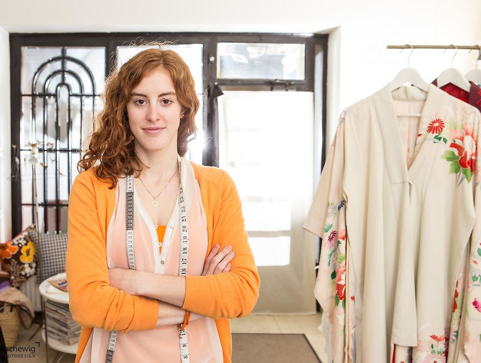 Junge Frau in ihrem Geschäft/Workshop, Wien, Österreich, Jungunternehmerin im Kreativbereich, Mode, Portrait, Maßband