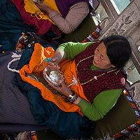 Tibetan woman pouring beads into her lap.