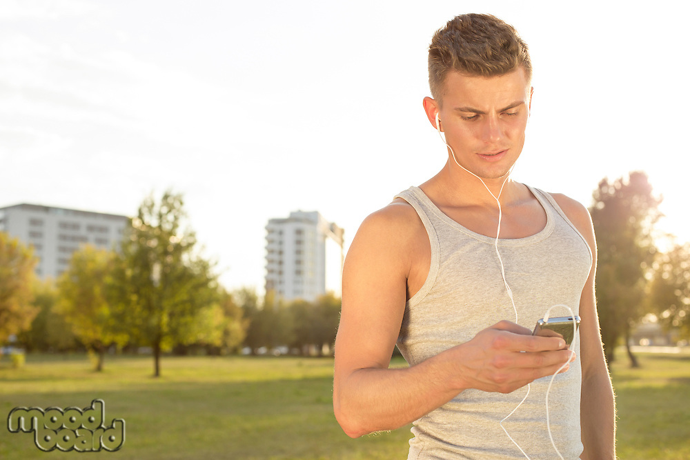 Young runner listening to music through cell phone in park