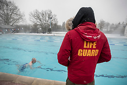 © Licensed to London News Pictures. 02/03/2018. London, UK. A life guard watches as swimmers brave the cold and snow at Hampton Pool in south west London. The 'Beast from the East' and Storm Emma have brought extreme cold, ice and heavy snow to the UK. Photo credit: Peter Macdiarmid/LNP