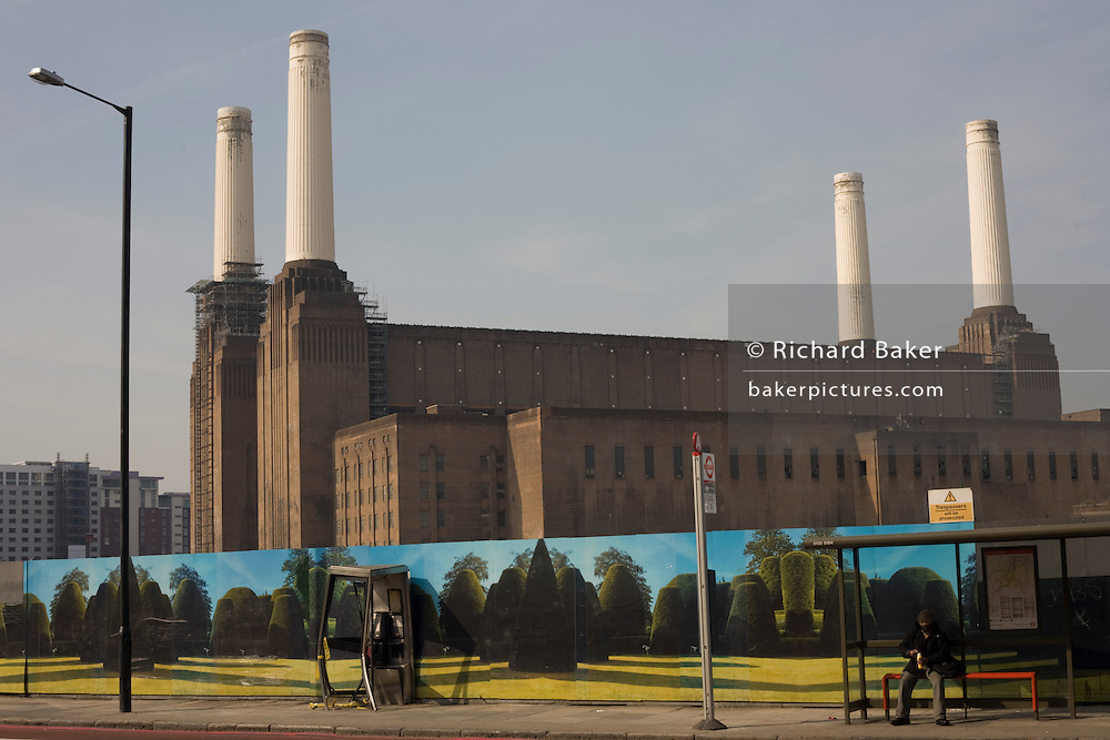 The four great chimneys of the Grade II listed Battersea Power Station rise to become one of South London's most notorious landmarks. In the foreground on Battersea Park Road is construction hoardings that yew hedges that act as an incongruous background with a bent phone box, recently damaged in a collision, and a bus stop at which a passenger awaits the next bus. Once a coal-fired power station located on the south bank of the River Thames, near Battersea in London, Battersea A Power Station was built first in the 1930s, with Battersea B Power Station to its east in the 1950s. The two stations were built to an identical design, providing the well known, four chimney layout. The station was decommissioned from generating electricity in 1983. The was used in The Beatles' 1965 movie Help! and on the cover of Pink Floyd's 1977 album Animals.
