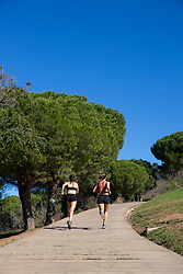 Two Women Running Uphill on Decked Path in Park