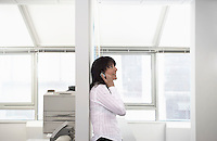 Female office worker using mobile phone leaning against column in office side view