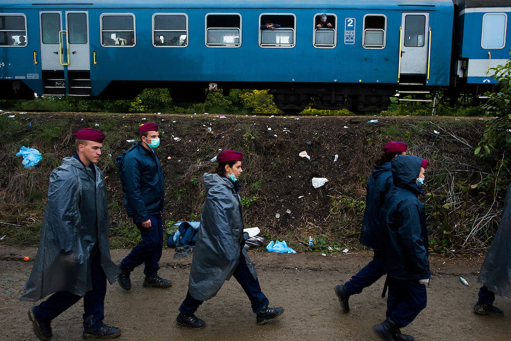Members of Hungarian law enforcement walk past a train filled with migrants near the Croatian border on September 25, 2015 in Zakany, Hungary.