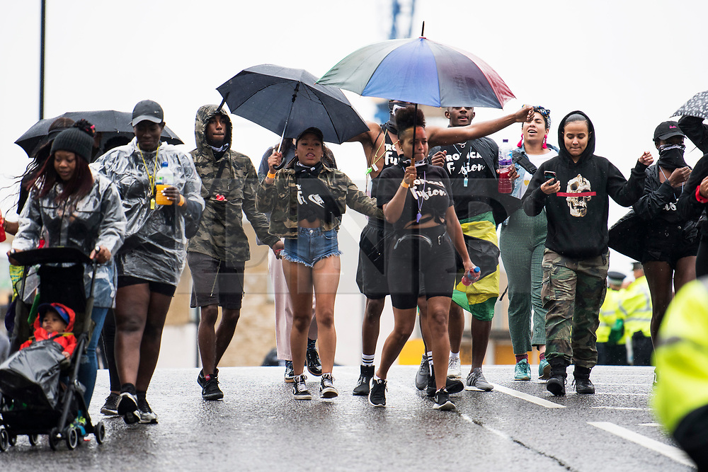 © Licensed to London News Pictures. 26/08/2018. London, UK. Young carnival goers shelter under an umbrella at family day of the 2018 Notting Hill Carnival. Up to 1 million people are expected to attend this weekend's event that is one of the worlds largest street festivals. Photo credit: Ben Cawthra/LNP