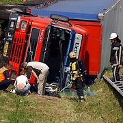 NLD/Blaricum/20050711 - Gekantelde vrachtwagen met gewonde chauffeur snelweg A27 ter hoogte Blaricum.kapotte voorruit, brandweer, vangrail, hulp