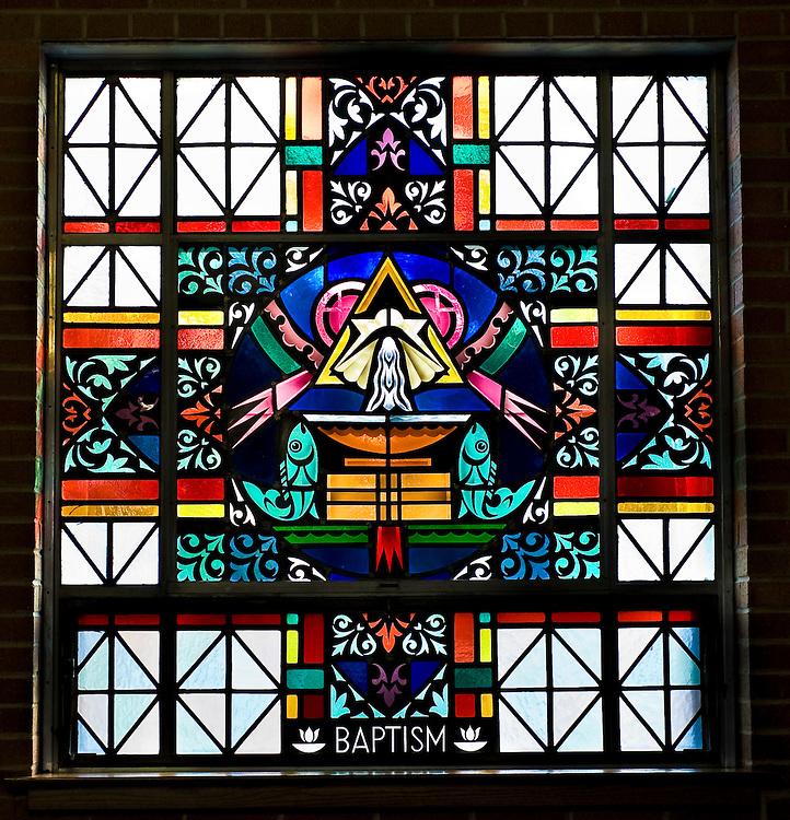 Stained glass image illustrating Sacrament of Baptism at St. Mary Church in Peshtigo, Wis. (Sam Lucero photo)