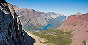 """See Elizabeth Lake and Belly River Valley from Ptarmigan Tunnel in Glacier National Park, Montana, USA. In 1930, the Ptarmigan Tunnel was dug 183 feet through the Ptarmigan Wall for hikers from Many Glacier to reach the Belly River Valley. Since 1932, Canada and USA have shared Waterton-Glacier International Peace Park, which UNESCO declared a World Heritage Site (1995) containing two Biosphere Reserves (1976). Rocks in the park are primarily sedimentary layers deposited in shallow seas over 1.6 billion to 800 million years ago. During the tectonic formation of the Rocky Mountains 170 million years ago, the Lewis Overthrust displaced these old rocks over newer Cretaceous age rocks. Glaciers carved spectacular U-shaped valleys and pyramidal peaks as recently as the Last Glacial Maximum (the last """"Ice Age"""" 25,000 to 13,000 years ago). Of the 150 glaciers existing in the mid 1800s, only 25 active glaciers remain in the park as of 2010, and all may disappear by 2020, say climate scientists. (Panorama stitched from 2 overlapping images.)"""