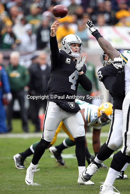 Oakland Raiders quarterback Derek Carr (4) throws a pass despite pressure from an outstretched hand during the 2015 week 15 regular season NFL football game against the Green Bay Packers on Sunday, Dec. 20, 2015 in Oakland, Calif. The Packers won the game 30-20. (©Paul Anthony Spinelli)