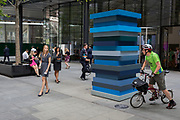 A side-glance between a young woman and a cyclist in front of the artwork entitled Stack Blues by Sean Scully RA, on 25th July 2018, in the City of London. Part of Scully's Landline series of works, Stack Blues is a sculpture borne out of the artist's preoccupation with the horizon.