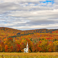 New England fall foliage peak colors framing the iconic Wonalancet Union Church in Tamworth, New Hampshire. It was my first visit and approaching the location just blew me away. I quickly pulled over and explored certain perspectives and in this image made my way into the field with a wide angle lens. I loved how this classic New England Photography subject was framed by the colorful autumn foliage. <br />