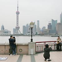 China, Shanghai,7-7-2008.. De Bund, de koloniale boulevard langs de Huangpu-rivier. De boulevard is in 1992 veranderd in een brede wandelpromenade..Vanaf de Bund ziet u aan de overkant van de Huangpu het nieuwe Pudong verrijzen. Deze wijk moet het hart van de handel en financiën van Shanghai gaan worden. Aan de nieuwbouw wordt dan ook veel zorg besteed en u vindt er veel fraaie voorbeelden van moderne architectuur. Een kenmerkend gebouw in Pudong is de Televisietoren. U kunt er met een snelle lift naar boven en u hebt dan een weids uitzicht over oud en nieuw Shanghai..(onbewerkt).Moderne Gebouwen. Nieuwe wijk