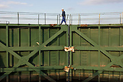 A worker walks across giant sea gates that are being repaired in Higashi-Matsushima,  Miyagi Prefecture on Feb. 24 2012. .Photographer: Robert Gilhooly