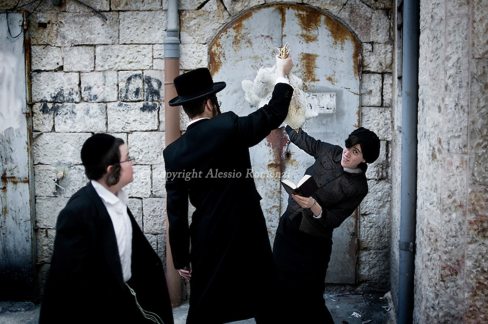 JERUSALEM : An Ultra-Orthodox Jewish man swings a chicken over his head during the Kaparot ceremony in Mea Shearim neighborhood of Jerusalem on October 6, 2011. The Jewish ritual is supposed to transfer the sins of the past year to the chicken, and is performed before the Day of Atonement, or Yom Kippur, the most important day in the Jewish calendar, which this year will start on sunset on October 7. ALESSIO ROMENZI