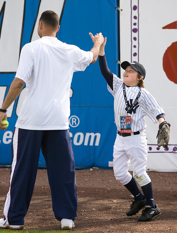 """Bryce Porter gets a high five from the New York Yankee's Derek Jeter  during the Upper Deck, """"Play Ball! with Derek Jeter"""" clinic on Saturday, February 10, 2007 at Legends Field in Tampa, Florida.   Justin Topa, 15, of Binghampton, New York, Jordan Boone, 10, of Las Vegas, Nevada, Bryce Porter, 10, of Costa Mesa, California and Gavin Leonard, 9, of Bristol, Virginia, each won the grand prize to meet Jeter through various promotions on www.UpperDeckKids.com in 2006 .UPPER DECK/Scott Audette"""