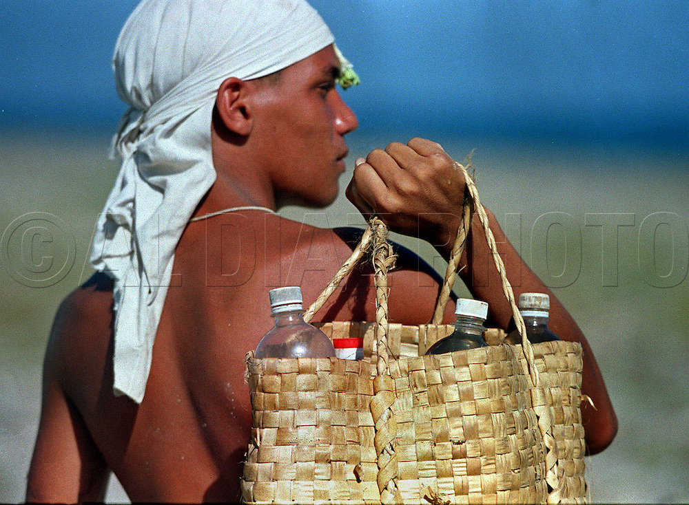 In 1994 Cuban balseros turned the tiny fishing village of Cojimar into a major point of embarkation for thousands seeking a better life. Here, Alex Castillo del Campo, 18, carries bottles of water in preparation of his long voyage on a makeshift raft departing Cojimar Cuba.