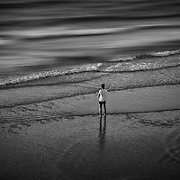 Conceptual beach scene with male figure standing alone