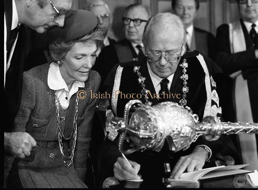 Nancy Reagan .Visits the Royal College Of Surgeons..St Stephens Green,.1984..04.06.1984.06.04.1984.4th June 1984..Nancy Reagan visited the Royal College of Surgeons where she unveilled a portrait of her late father.Her father, Dr Loyal Davis was an Honorary Fellow of the college. Mrs Reagan then presented the portrait to the college..Under the shadow of the college mace Professor O'Malley signs the commerative book for Mrs Nancy Reagan.