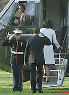 President Barack Obama salutes Marine guard as  he and First Lady Michelle Obama board Marine One on their way to Andrews Air Force Base and Air Force One which will take them to London for the Economic Summit. Photograph by Dennis Brack