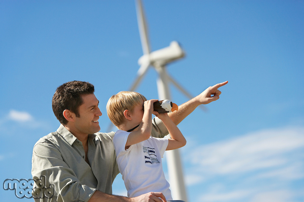 Boy (7-9) using binoculars with father at wind farm