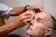 Tucson, Arizona, USA, August 16, 2014: Dr. Lansing Brown, (left), provides a free healthy eye screening for Richard Hicks, 74, as part of the UAMC Sight Savers Program.  The screening checks for cataracts, glaucoma, diabetes, macular degeneration and dry eye and is sponsored by the Department of Ophthalmology, The University of Arizona Medical Center, Alvernon Physician Offices, Tucson, Arizona, USA.