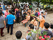 """21 JULY 2013 - BANGKOK, THAILAND:   The families of men entering the monastery for Vassa have their hair cut by members of their families at Wat Benchamabophit on the first day of Vassa, the three-month annual retreat observed by Theravada monks and nuns. Men frequently enter the monastery and become Buddhist monks for Vassa. On the first day of Vassa (or Buddhist Lent) many Buddhists visit their temples to """"make merit."""" During Vassa, monks and nuns remain inside monasteries and temple grounds, devoting their time to intensive meditation and study. Laypeople support the monastic sangha by bringing food, candles and other offerings to temples. Laypeople also often observe Vassa by giving up something, such as smoking or eating meat. For this reason, westerners sometimes call Vassa the """"Buddhist Lent.""""      PHOTO BY JACK KURTZ"""