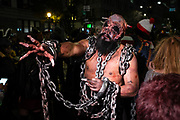 New York, NY - 31 October 2019. the annual Greenwich Village Halloween Parade along Manhattan's 6th Avenue. A chained and shackled man with a gory mask and a nail through his head.