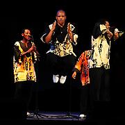 Ladysmith Black Mambazo member Msizi Shabalala (c) leaping into the air at The Music Hall, Portsmouth, NH