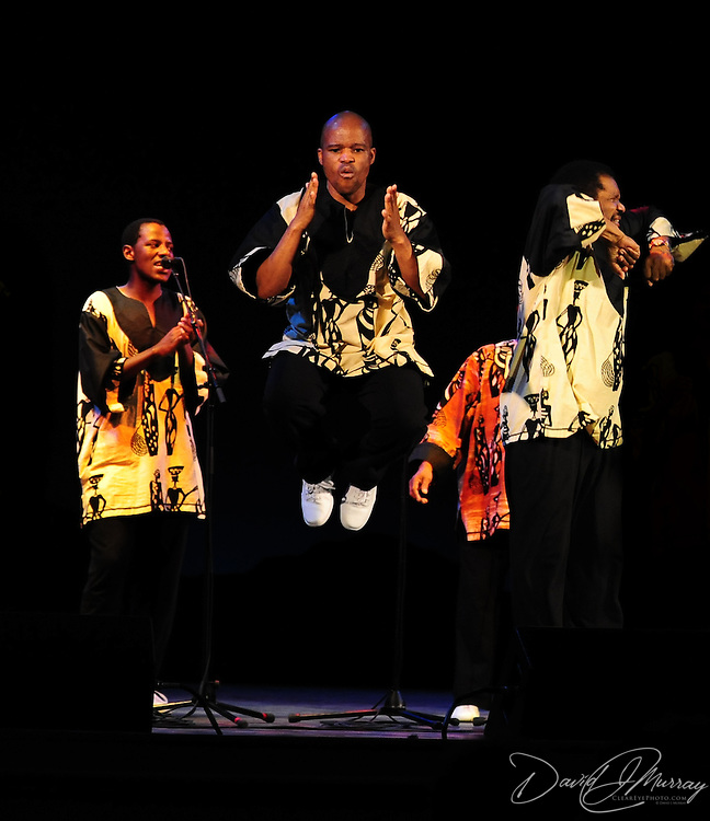 Ladysmith Black Mambazo member Msizi Shabalala (c) leaping into the air at The Music Hall, Portsmouth, NH