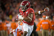 Alabama running back #9 Bo Scarbrough scores the first touchdown of the game, on a 25 yard run, during first quarter action of the national championship game at Raymond James stadium in Tampa. Ryan Carter #31 of Clemson is in pursuit.
