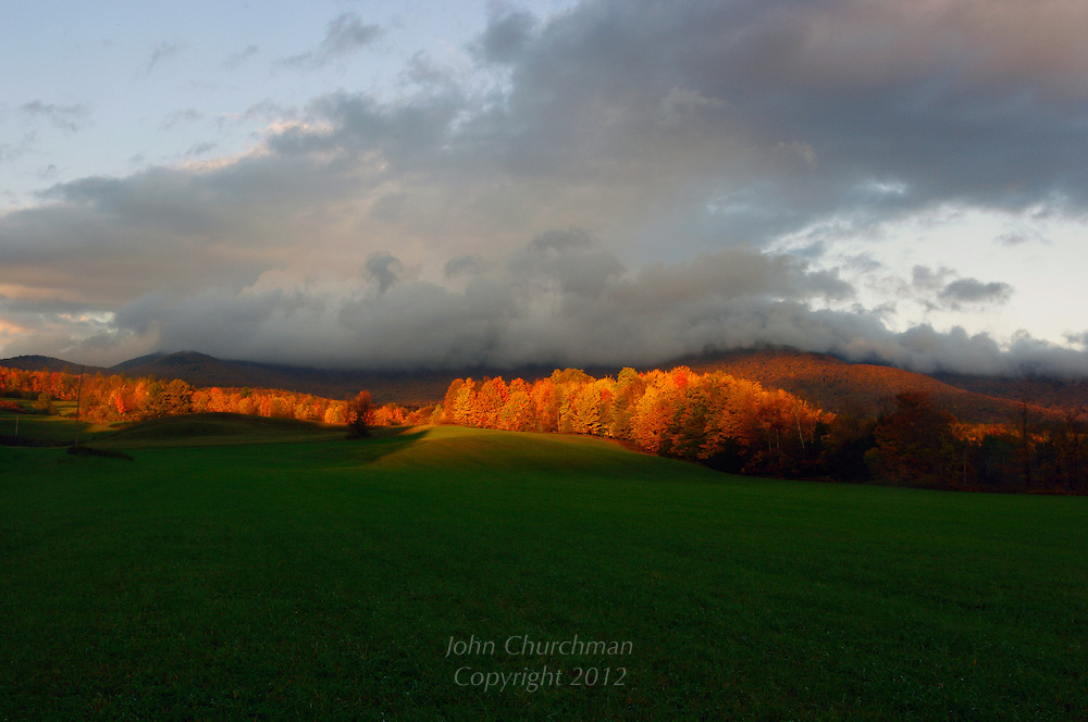 Fall scene with sunlight and dark clouds