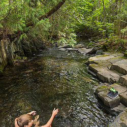 A boy swims at Red River Falls in Aroostook County, Maine. Deboullie Public Reserve Land.