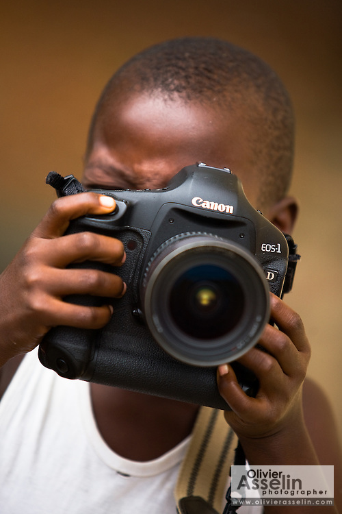 Young boy playing with professional camera at the NDA health center in Dimbokro, Cote d'Ivoire on Friday June 19, 2009.