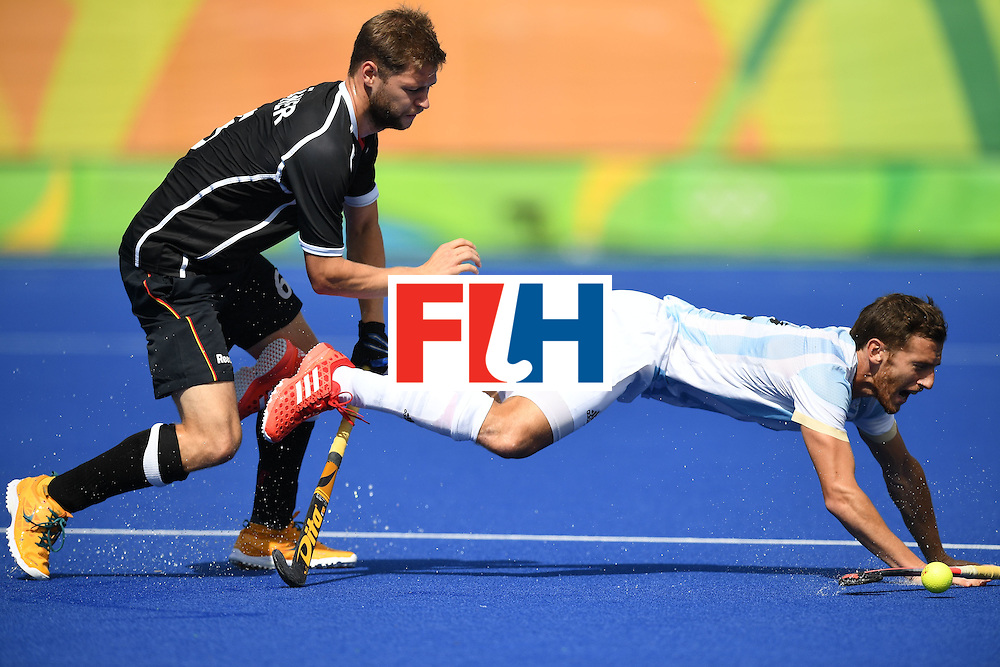 Germany's Martin Haner (L) falls over Argentina's Gonzalo Peillat during the men's field hockey Argentina vs Germany match of the Rio 2016 Olympics Games at the Olympic Hockey Centre in Rio de Janeiro on August, 11 2016. / AFP / MANAN VATSYAYANA        (Photo credit should read MANAN VATSYAYANA/AFP/Getty Images)