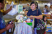 07 AUGUST 2012 - TOLLESON, AZ:  A client picks up food for her family at the food bank in Tolleson, AZ, about 15 miles west of Phoenix. The Tolleson food bank has been operating for more than 20 years. It used to serve mostly the families of migrant farm workers that worked the fields around Tolleson but in the early 2000's many of the farms were sold to real estate developers. Now the food bank serves both farm worker families and people who lost their homes in the real estate crash, that his Phoenix suburbs especially hard. More than 150 families a day are helped by the Tolleson food bank, an increase of more than 50% in the last five years.  PHOTO BY JACK KURTZ