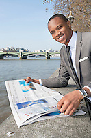 Portrait of African American businessman reading newspaper