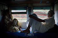 Pilgrims Jamnadas Prajapati aged 80 and his wife of 59 years, Shanti aged 65, watch Madhya Pradesh pass by as they travel for the 3rd time from Jhansi, Uttar Pradesh, to Kanyakumari to visit the Ramanathaswamy Temple. Jamnadas is a former railway employee and is allowed to travel free of charge, by train to anywhere in India twice a year...Train passengers on the Himsagar Express 6318 going from Jammu Tawi station to Kanyakumari on 8th July 2009.. .6318 / Himsagar Express, India's longest single train journey, spanning 3720 kms, going from the mountains (Hima) to the seas (Sagar), from Jammu and Kashmir state of the Indian Himalayas to Kanyakumari, which is the southern most tip of India...Photo by Suzanne Lee / for The National