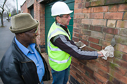 Building repointing a brick wall while his client looks on,