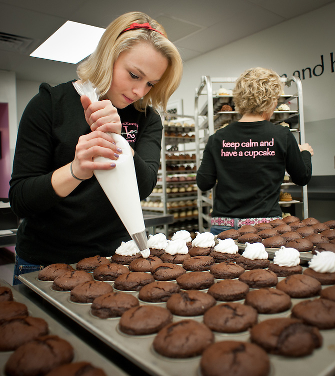 ELKRIDGE, MD -- 12/23/11 - Amanda ices a rack of cupcakes while her mother moves a rack of them in the background. Amanda plays a pivotal role in the formation of the business....Michelle Kupiec owns Kupcakes and Co., and specializes in cupcakes made from scratch. Her two daughters, Amanda and Allison help with the business, with Amanda coming up with most of the recipes, and Allison typically working the front counter. Though only open for about six months, they are already selling 10,000 cupcakes per week, including orders from six restaurants locally. …by André Chung #AC1_3087
