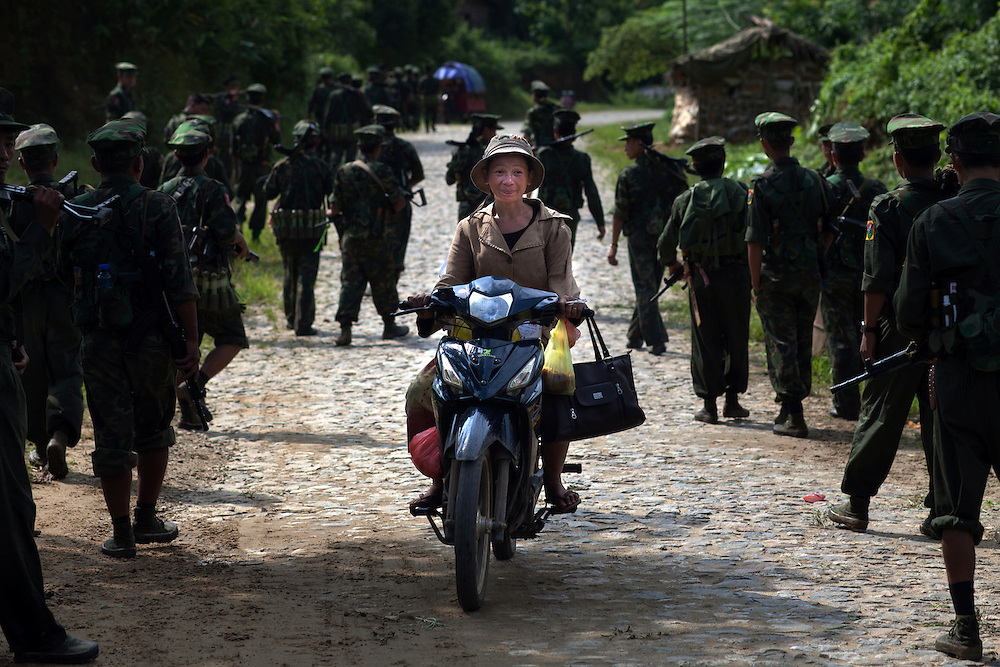 A Kachin woman pass through a KIA's battalion with her moped while they come back to Laiza from the front line, Kachin State, Myanmar on August 8, 2012. Since 1960 Kachin people are in war against Burma Government is the largest war in the world. The KIA formed in 1961 in response to a military coup in Burma led by General Ne Win, who attempted to consolidate Burmese control over regions on the periphery of the state which were home to various ethnic groups. From 1961 until 1994, the KIA fought a grueling and inconclusive war against the Burmese junta. In 2011, general Sumlut Gun Maw confirmed renewed fighting in the state of Kachin for independence. One of the new reasons for the ending of the ceasefire is the creation of the Myitsone Dam which requires the submergence of dozens of villages in Kachin state.