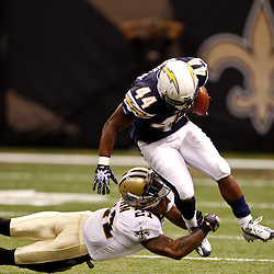 August 27, 2010; New Orleans, LA, USA; New Orleans Saints safety Chip Vaughn (21) nearly loses his helmet as he tackles San Diego Chargers running back Curtis Brinkley (44)  during the second half of a preseason game at the Louisiana Superdome. Mandatory Credit: Derick E. Hingle