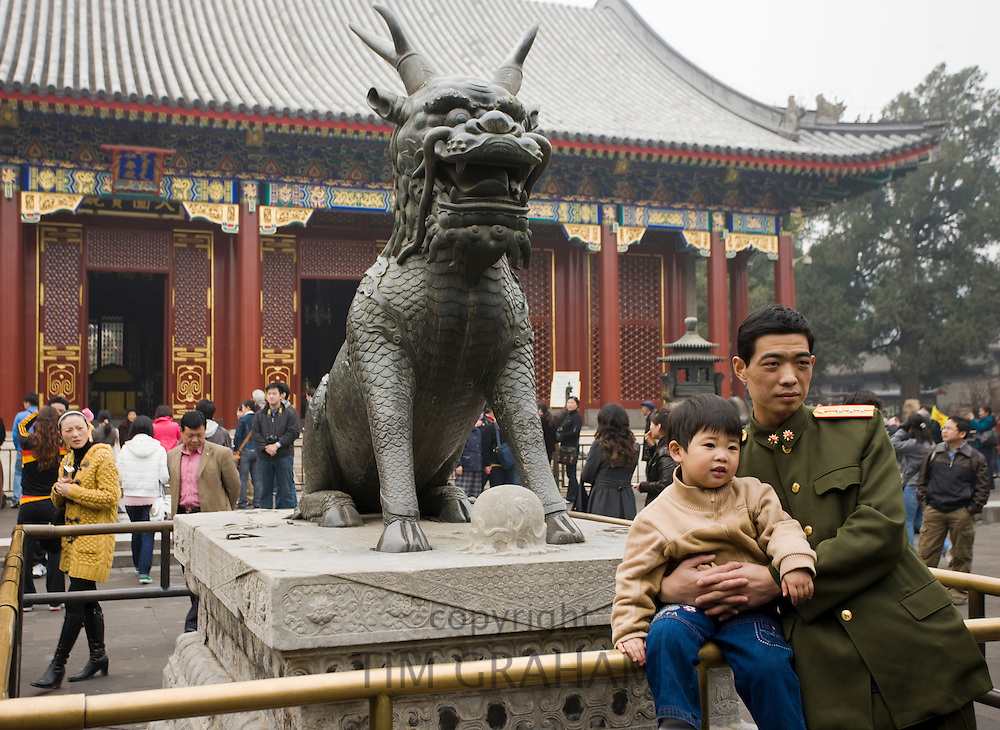 Father and son by Qilin statue, Summer Palace, Beijing. China has a one child family policy to limit population.