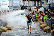This was at my first Sheringham Carnival Street Races along the High Street. I would normally go to the far end with the competitors running towards me, but after seeing how lawless it can be and how anybody who went down there was a target with flour and water throwers. I decided to stay well away in the relative safe zone near the clock tower. I really like how the waitress i making her way back through the mayhem, you can see a ballon about to hit her and a cloud of flour which help to separate her from the background. <br /> <br /> Picture: MARK BULLIMORE