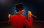 Against the strong spotlight of the Big Top, a ringmaster announces the next act during an afternoon performance by the Gerry Cottle circus in North London. With his top hat perched firmly on his head and holding his microphone, the leader of his troupe smiles confidently and speaks with authority to the unseen audience who eagerly await the skills of acrobats or clowns who are about to enter the ring. In his scarlet red coat and holding a pair of gloves in his other hand, the man is the epitome of showmen - a picture of show businesses and variety, of the presenter from another era.