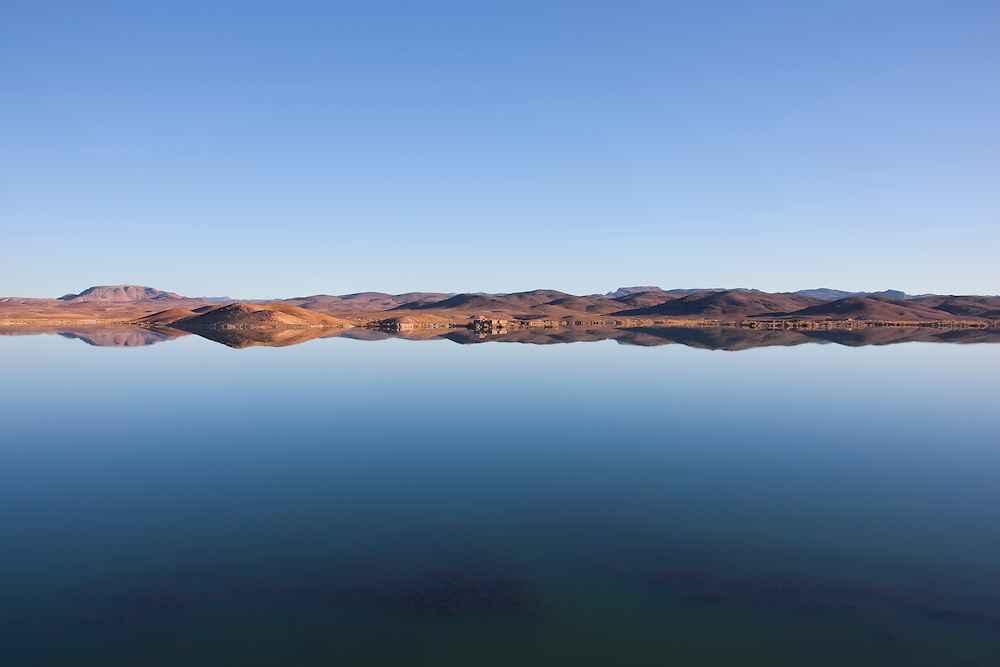 El-Mansour Eddabbi dam with mountain reflections in Ouarzazate, Morocco.
