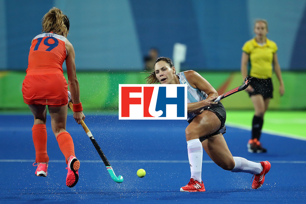 RIO DE JANEIRO, BRAZIL - AUGUST 15:  Noel Barrionuevo #27 of Argentina passes the ball past Ellen Hoog #19 of Netherlands during the quarter final hockey game on Day 10 of the Rio 2016 Olympic Games at the Olympic Hockey Centre on August 15, 2016 in Rio de Janeiro, Brazil.  (Photo by Christian Petersen/Getty Images)