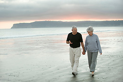 Senior couple out walking the beach at dusk