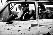 Men in a shot-up Volkswagen Golf car prepare to depart after delivering a wounded man to City Hospital during the Bosnian Serb siege of Sarajevo, August 1992. (Photo by Roger Richards)