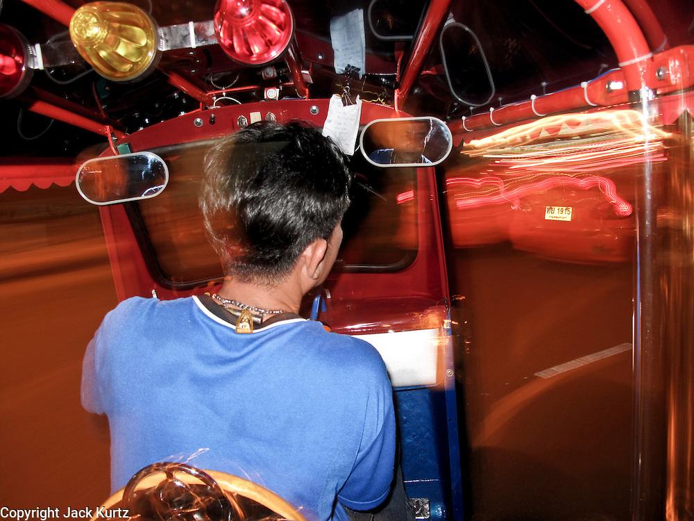 "Mar. 21, 2009 -- BANGKOK, THAILAND: Riding in the back of a ""tuk-tuk,"" a three wheeled taxi popular with tourists, in Bangkok, Thailand. Photo by Jack Kurtz"