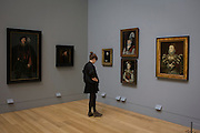 A young woman admires Tudor portraits of Elizabethan nobility in Tate Britain, London.